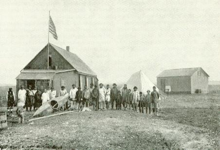The crew standing around a small house, tent, and outbuilding with no snow