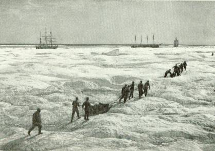men dragging sleds across a field of ice towards ships in the distance