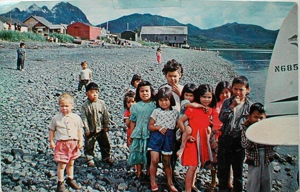 Children meeting a floatplane at Old Harbor, Alaska in the 1950s.