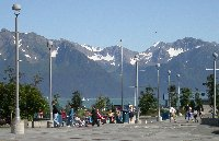 People enjoy the sunshine from the square in front of the Sealife Center in Seward, Alaska