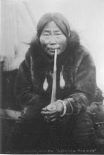 'Eskimo woman hitting the pipe.' Photo by F. H. Nowell of Nome.