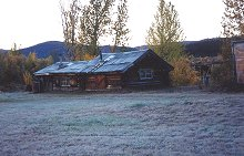 Jimmy Lynch's cabin on Big Gold Creek, beside the dredge. Sixtymile gold district, Yukon Territory